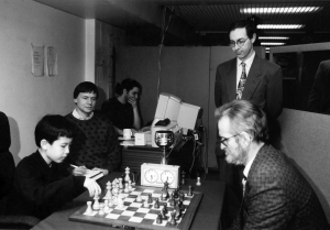 Andrew Whiteley playing a challenge match against 9-year-old David Howell in the year 2000. I am in the picture too as I was scoring the game. Looking on is Barry Gale, organiser of the Kensington tournaments at the time, and Alexis Harakis is at the computer analysing the game on Fritz.